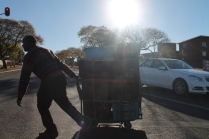 Mudzvamuse crosses a busy WF Nkomo (Church) Street intersection in the late afternoon sun.