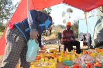 A customer buys skopasie (flavoured popcorn). Mudzvamuse sells vegetables, fruits, flavoured popcorn, cigarettes, and even chalk stones, which are also eaten. When he came to South Africa he had R350 in his pocket, most of which was spent on rent. Having no money for a taxi, he walked the approximately four kilometres to Marabastad and bought a packet of 32 oranges for R9. He sold them all in a few hours for R1 each, making triple the money back. Mudzvamuse expanded his offerings and makes just enough money to put his children through school, pay R600 at a new place, buy more stock and support his family.